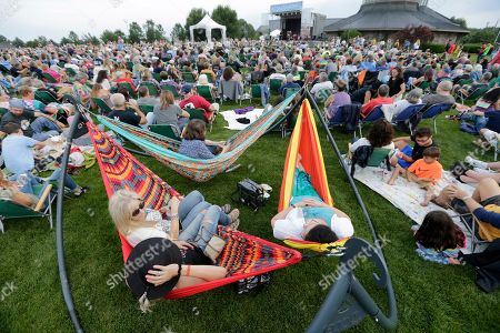 People enjoy a concert by Arlo Guthrie at a Woodstock 50th anniversary event in Bethel, N.Y., . Bethel Woods Center for the Arts is hosting a series of events Thursday through Sunday at the bucolic 1969 concert site, 80 miles (130 kilometers) northwest of New York City