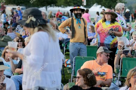 People arrive and find their seats for an Arlo Guthrie concert at a Woodstock 50th anniversary event in Bethel, N.Y., . Bethel Woods Center for the Arts is hosting a series of events Thursday through Sunday at the bucolic 1969 concert site, 80 miles (130 kilometers) northwest of New York City