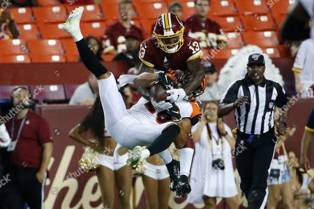 Kelvin Harmon, Jordan Brown. Washington Redskins wide receiver Kelvin Harmon (13) and Cincinnati Bengals defensive back Jordan Brown (26) get tangled up as they both go for a pass during the second half of an NFL preseason football game, in Landover, Md. The Bengals won 23-13