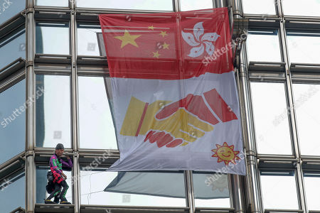 Alain Robert, a French rock and urban climber hangs a large fabric displaying Chinese and Hong Kong flags, shaking hands and shining sun in Cheung kong centre building in Hong Kong, . Flights resumed at Hong Kong's airport Wednesday morning after two days of disruptions marked by outbursts of violence that highlight the hardening positions of pro-democracy protesters and the authorities in the semi-autonomous Chinese city