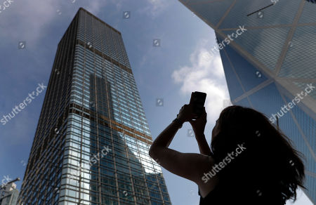A woman takes a photo of Cheung kong centre building in which Alain Robert, a French rock and urban climber hung a large fabric displaying Chinese and Hong Kong flags, shaking hands and shining sun in Hong Kong, . Flights resumed at Hong Kong's airport Wednesday morning after two days of disruptions marked by outbursts of violence that highlight the hardening positions of pro-democracy protesters and the authorities in the semi-autonomous Chinese city