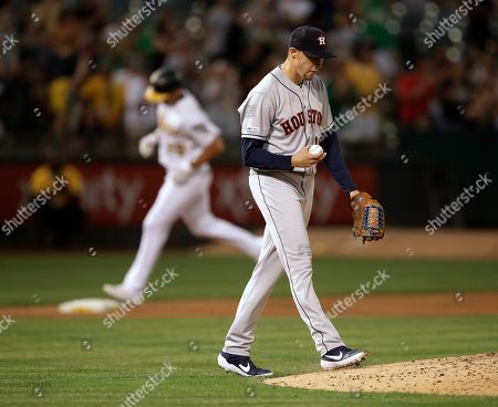 Houston Astros' Aaron Sanchez, right, walks back to the mound after giving up a three-run home run to Oakland Athletics' Matt Olson, rear, in the fourth inning of a baseball game, in Oakland, Calif