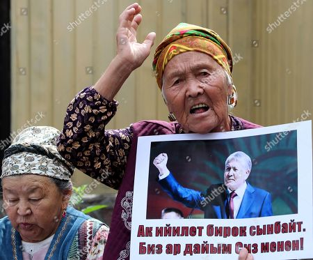 A Kyrgyz woman with a poster near the building of the State Committee for National Security, during a Bishkek rally in Kyrgyzstan on 16 August 2019. The posters read 'Light power bends but does not break'.. The court decided to leave the ex-president of the country Almazbek Atambayev in custody in the GKNB pre-trial detention center until 26 August 2019.