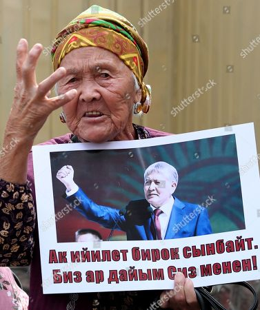 A Kyrgyz woman with a poster near the building of the State Committee for National Security, during a Bishkek rally in Kyrgyzstan on 16 August 2019. The posters read 'Light power bends but does not break'. The court decided to leave the ex-president of the country Almazbek Atambayev in custody in the GKNB pre-trial detention center until 26 August 2019.