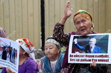 Stock Picture of A Kyrgyz woman with a poster near the building of the State Committee for National Security, during a Bishkek rally in Kyrgyzstan on 16 August 2019. The posters read 'Light power bends but does not break'. The court decided to leave the ex-president of the country Almazbek Atambayev in custody in the GKNB pre-trial detention center until 26 August 2019.