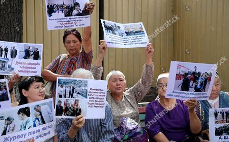 Stock Image of Kyrgyz women with posters near the building of the State Committee for National Security, during a Bishkek rally in Kyrgyzstan on 16 August 2019. The posters read 'Light power bends but does not break,' 'Atambaev is always with the people,' 'A pure heart always bears good,' 'Atambayev is the son of his people'. The court decided to leave the ex-president of the country Almazbek Atambayev in custody in the GKNB pre-trial detention center until 26 August 2019.