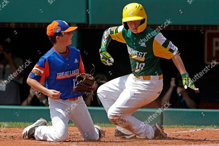 Stock Image of Coon Rapids, Minnesota's Tyler Phillips (18) scores ahead of the tag by Bowling Green, Kentucky's Grayson Newman during the second inning of a baseball game at the Little League World Series tournament in South Williamsport, Pa., . Minnesota won 2-1
