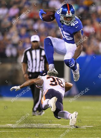 New York Giants running back Rod Smith (45) leaps to avoid a tackle by Chicago Bears defensive back Clifton Duck (38) during an NFL football game, in East Rutherford, N.J