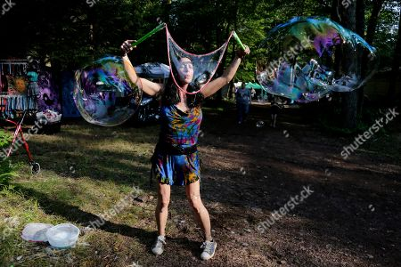 """Sarah Drake blows bubbles at a celebration of Woodstock on a piece of the original Yasgur farm in Bethel, N.Y., . Tie-dyed pilgrims and white-haired Woodstock festival veterans converged at the generation-defining site to celebrate its 50th anniversary, while Arlo Guthrie came back to sing ? what else? ? """"The Times They Are a-Changin'."""" Along with other local celebrations, Bethel Woods Center for the Arts is hosting a series of events at the bucolic 1969 concert site, 80 miles (130 kilometers) northwest of New York City"""