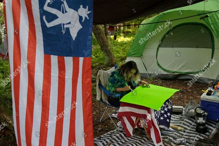 """Meghan Arminas makes a poster while camping at a celebration of Woodstock on a piece of the original Yasgur farm in Bethel, N.Y., . Tie-dyed pilgrims and white-haired Woodstock festival veterans converged at the generation-defining site to celebrate its 50th anniversary, while Arlo Guthrie came back to sing ? what else? ? """"The Times They Are a-Changin'."""" Along with other local celebrations, Bethel Woods Center for the Arts is hosting a series of events at the bucolic 1969 concert site, 80 miles (130 kilometers) northwest of New York City"""