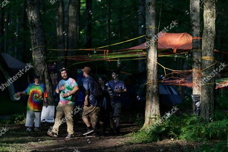 """People walk through the woods at celebration of Woodstock on a piece of the original Yasgur farm in Bethel, N.Y., . Tie-dyed pilgrims and white-haired Woodstock festival veterans converged at the generation-defining site to celebrate its 50th anniversary, while Arlo Guthrie came back to sing ? what else? ? """"The Times They Are a-Changin'."""" Along with other local celebrations, Bethel Woods Center for the Arts is hosting a series of events at the bucolic 1969 concert site, 80 miles (130 kilometers) northwest of New York City"""