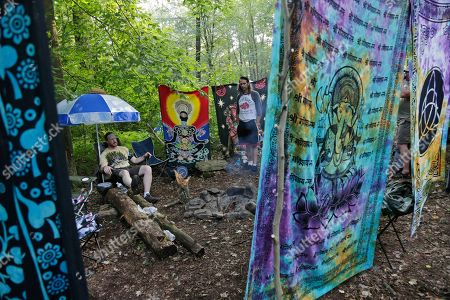 """People relax at their campsite during a celebration of Woodstock on a piece of the original Yasgur farm in Bethel, N.Y., . Tie-dyed pilgrims and white-haired Woodstock festival veterans converged at the generation-defining site to celebrate its 50th anniversary, while Arlo Guthrie came back to sing ? what else? ? """"The Times They Are a-Changin'."""" Along with other local celebrations, Bethel Woods Center for the Arts is hosting a series of events at the bucolic 1969 concert site, 80 miles (130 kilometers) northwest of New York City"""