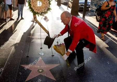 """Unofficial Hollywood ambassador Gregg Donovan places flowers on the Walk of Fame star of Peter Fonda, in Los Angeles. Fonda, the son of a Hollywood legend who became a movie star in his own right both writing and starring in counterculture classics like """"Easy Rider,"""" has died. His family says in a statement that Fonda died Friday at his home in Los Angeles. He was 79"""