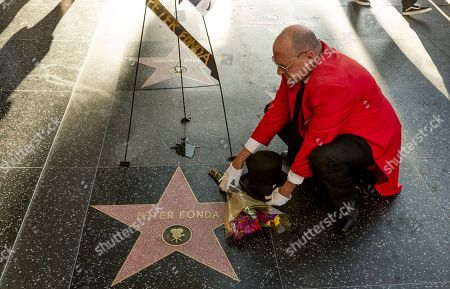 """Unofficial Hollywood ambassador Gregg Donovan sets flowers on the Walk of Fame star of Peter Fonda in Los Angeles . Peter Fonda, the son of a Hollywood legend who became a movie star in his own right both writing and starring in counterculture classics like """"Easy Rider,"""" has died. His family says in a statement that Fonda died Friday, Aug. 16, 2019, at his home in Los Angeles. He was 79"""