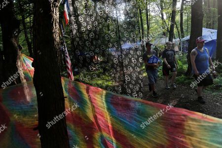 """Stock Photo of People walk through the woods at celebration of Woodstock on a piece of the original Yasgur farm in Bethel, N.Y., . Tie-dyed pilgrims and white-haired Woodstock festival veterans converged at the generation-defining site to celebrate its 50th anniversary, while Arlo Guthrie came back to sing ? what else? ? """"The Times They Are a-Changin'."""" Along with other local celebrations, Bethel Woods Center for the Arts is hosting a series of events at the bucolic 1969 concert site, 80 miles (130 kilometers) northwest of New York City"""