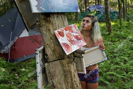 """Alyssa Shann hangs some of her artwork on tree stump during a celebration of Woodstock on a piece of the original Yasgur farm in Bethel, N.Y., . Tie-dyed pilgrims and white-haired Woodstock festival veterans converged at the generation-defining site to celebrate its 50th anniversary, while Arlo Guthrie came back to sing ? what else? ? """"The Times They Are a-Changin'."""" Along with other local celebrations, Bethel Woods Center for the Arts is hosting a series of events at the bucolic 1969 concert site, 80 miles (130 kilometers) northwest of New York City"""