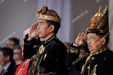 Indonesian President Joko Widodo (L) and his Vice President Jusuf Kalla (R) wearing traditional costumes, salute during a flag raising ceremony to mark the 74th Independence Day at Merdeka Palace in Jakarta, Indonesia, 17 August 2019. Indonesia gained independence from the Netherlands in 1945.