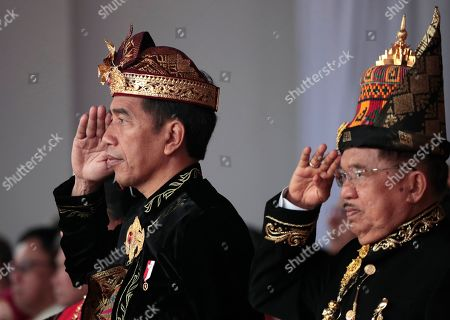 Indonesian President Joko Widodo, left, and his deputy Jusuf Kalla, right, salute during a flag hoisting ceremony commemorating the country's 74th anniversary of independence at Merdeka Palace in Jakarta, Indonesia, . Indonesia gained its independence in 1945 from the Dutch colonial rule
