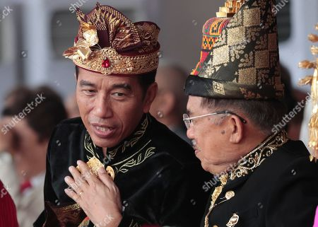 Dressed in traditional outfit, Indonesian President Joko Widodo, left, confers with his deputy Jusuf Kalla during a flag hoisting ceremony commemorating the country's 74th anniversary of independence at Merdeka Palace in Jakarta, Indonesia, . Indonesia gained its independence in 1945 from the Dutch colonial rule