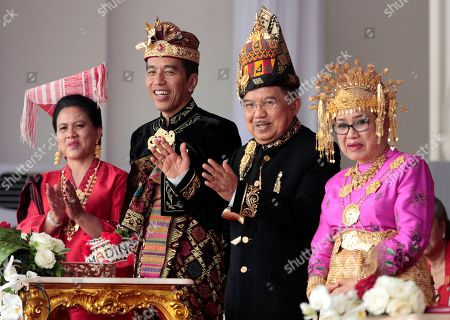 Dressed in traditional outfits, Indonesian President Joko Widodo, second from left, his wife Iriana, left, and his deputy Jusuf Kalla, second from right, and his wife Mufidah, attend a flag hoisting ceremony commemorating the country's 74th anniversary of independence at Merdeka Palace in Jakarta, Indonesia, . Indonesia gained its independence in 1945 from the Dutch colonial rule