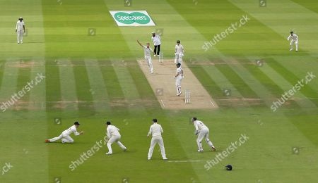 England's Rory Burns, bottom left takes a catch to dismiss Australia's Matthew Wade, as England's bowler Stuart Broad, top centre, celebrates during play on day four of the 2nd Ashes Test cricket match between England and Australia at Lord's cricket ground in London