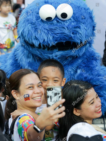 A woman with her child poses for a selfie with 'Cookie Monster' from the Sesame Street show during the 'Sesame Street Run' in Manila, Philippines, 17 August 2019. The Sesame Street Run is a family run catered for all ages to celebrate the 50 years anniversary of the educational 'Sesame Street' show featuring the fluffy characters called muppets by US puppeteer Jim Henson. The Sesame Street Run will travel and also be held in Thailand, Malaysia, Indonesia, and Singapore. 'Sesame Street' premiered on US television on 10 November 1969.