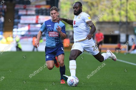 Milton Keynes Dons midfielder Hiram Boateng (26) gets his cross away under pressure from Wycombe Wanderers midfielder Dominic Gape (4) during the EFL Sky Bet League 1 match between Wycombe Wanderers and Milton Keynes Dons at Adams Park, High Wycombe