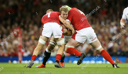 Joe Launchbury of England is tackled by  James Davies of Wales (L) & Jake Ball of Wales