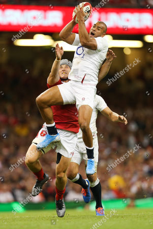 Jonathan Joseph of England takes the ball under pressure from Jonathan Davies of Wales