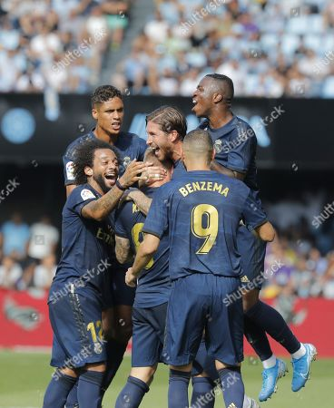 Real Madrid's German Toni Kroos (C, backwards) celebrates with his teammates Marcelo (L), Raphael Varane (2-L), Sergio Ramos (3-R), Vinicius Jr. (R) and Karim Benzema (2-R) after scoring against Celta Vigo during their LaLiga game at Balaidos Stadium, in Vigo, northwestern Spain, 17 August 2019.