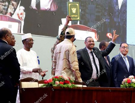 Stock Picture of Sudan's Forces of Freedom and Change coalition leader Ahmad al-Rabiah (3-R) flashes a victory sign after signing the power sharing agreement (green document at Top) with Sudan's General and Vice President of Sudanese Transitional Military Council, Mohamed Hamdan Dagalo (3-L), as international guests look on, in Khartoum, Sudan, 17 August 2019. According to reports, Sudan's Military council and opposition are to sign later in the day the power sharing agreement that has been negotiated for many months. The agreement sets up a sovereign council made of five generals and six civilians, to rule the country until general elections. Protests had erupted in Sudan at the end of 2018, culminating in a long sit-in outside the army headquarters which ended with more than one hundred people being killed and others injured. Sudanese President Omar Hassan al-Bashir stepped down on 11 April 2019.