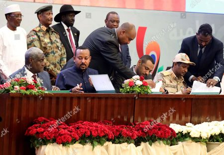 Stock Image of Sudan's Forces of Freedom and Change coalition leader Ahmad al-Rabiah (3-R) and Sudan's General and Vice President of Sudanese Transitional Military Council, Mohamed Hamdan Dagalo (2-R) sign power sharing agreement, as guests and partners look on, in Khartoum, Sudan, 17 August 2019. According to reports, Sudan's Military council and opposition are to sign later in the day the power sharing agreement that has been negotiated for many months. The agreement sets up a sovereign council made of five generals and six civilians, to rule the country until general elections. Protests had erupted in Sudan at the end of 2018, culminating in a long sit-in outside the army headquarters which ended with more than one hundred people being killed and others injured. Sudanese President Omar Hassan al-Bashir stepped down on 11 April 2019.