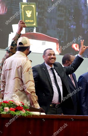 Sudan's Forces of Freedom and Change coalition leader Ahmad al-Rabiah (R) flashes a victory sign after signing the power sharing agreement (green document at Top) with Sudan's General and Vice President of Sudanese Transitional Military Council, Mohamed Hamdan Dagalo (L), as international guests look on, in Khartoum, Sudan, 17 August 2019. According to reports, Sudan's Military council and opposition are to sign later in the day the power sharing agreement that has been negotiated for many months. The agreement sets up a sovereign council made of five generals and six civilians, to rule the country until general elections. Protests had erupted in Sudan at the end of 2018, culminating in a long sit-in outside the army headquarters which ended with more than one hundred people being killed and others injured. Sudanese President Omar Hassan al-Bashir stepped down on 11 April 2019.