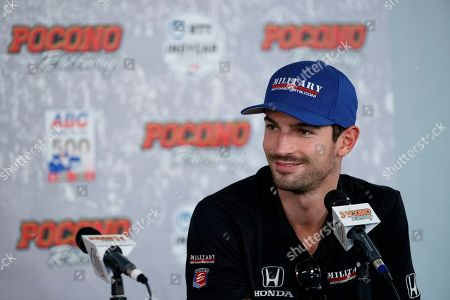 Alexander Rossi smiles during a news conference for Sunday's IndyCar Series auto race at Pocono Raceway, in Long Pond, Pa