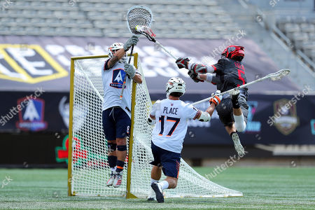 Stock Picture of Chaos' Connor Fields (5) leaps to shoot as Archers' goalie Adam Ghitelman (8) reaches for the save while Archers' Jackson Place (17) defends during a Premier Lacrosse League game on in Hamilton, Ontario
