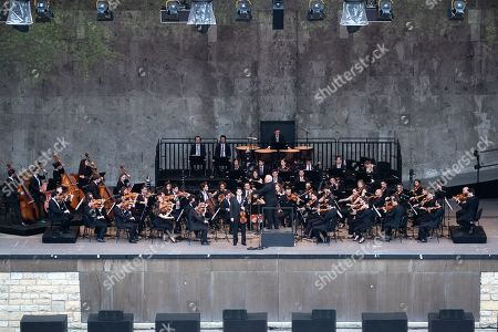Stock Image of Conductor Daniel Barenboim and the West-Eastern Divan Orchestra perform during its 20th anniversary concert at the Forest Stage (Waldbuehne) in Berlin, Germany, 17 August 2019. The orchestra is based in Seville, Spain, consisting of musicians from countries in the Middle East and Spanish background.