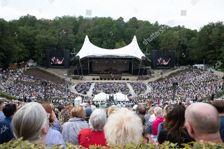 Stock Photo of Conductor Daniel Barenboim and the West-Eastern Divan Orchestra perform during its 20th anniversary concert at the Forest Stage (Waldbuehne) in Berlin, Germany, 17 August 2019. The orchestra is based in Seville, Spain, consisting of musicians from countries in the Middle East and Spanish background.