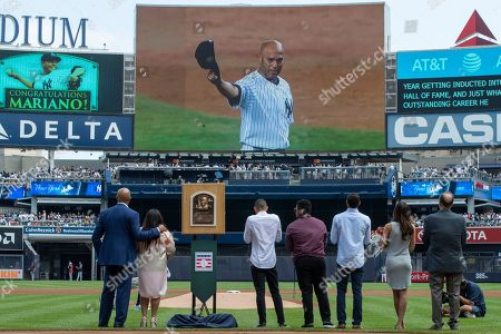 Mariano Rivera, Clara Rivera, Joe Torre. Former New York Yankees pitcher and National Baseball Hall of Fame inductee Mariano Rivera, left, joined by his wife Clara, members of his family and former New York Yankees manager Joe Torre, right, watch a video during a ceremony in his honor before a baseball game between the New York Yankees and the Cleveland Indians, in New York