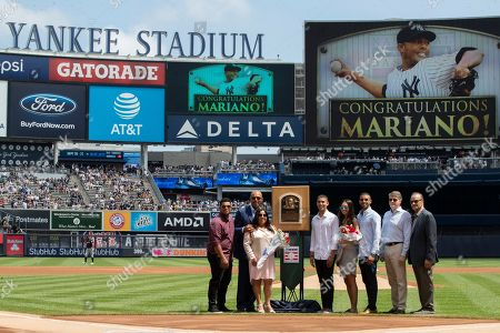 Mariano Rivera, Clara Rivera, Joe Torre, Hal Steinbrenner. Former New York Yankees pitcher and National Baseball Hall of Fame inductee Mariano Rivera, left, joined by his wife Clara, members of his family, former New York Yankees manager Joe Torre, right, and Hal Steinbrenner, second from right, pose for photographers during a ceremony in his honor before a baseball game between the New York Yankees and the Cleveland Indians, in New York