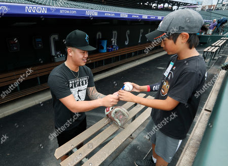 Wei yin chen, joe wani, r m. Miami Marlins relief pitcher Wei-Yin Chen, left, of Taiwan, hands an autographed ball back to 10-year-old Joe Wani, of Bellevue, Wash., in the Marlins dugout before a baseball game against the Colorado Rockies, in Denver