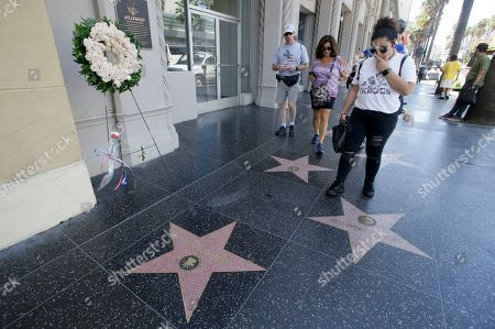 People approach a wreath and a set of flowers that stand next to actor Peter Fonda's star on the Walk of Fame on Hollywood Blvd. in Hollywood, California, USA, 17 August 2019. Fonda died on 16 August from lung cancer, he was the son of legendary actor Henry Fonda and starred in the 1969 classic movie 'Easy Rider.' He was 79.