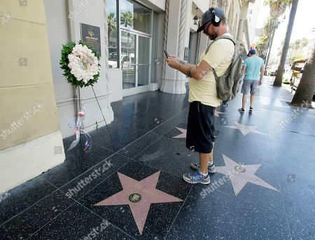 A man takes a photo of the wreath and a set of flowers that stand next to actor Peter Fonda's star on the Walk of Fame on Hollywood Blvd. in Hollywood, California, USA, 17 August 2019. Fonda died on 16 August from lung cancer, he was the son of legendary actor Henry Fonda and starred in the 1969 classic movie 'Easy Rider.' He was 79.