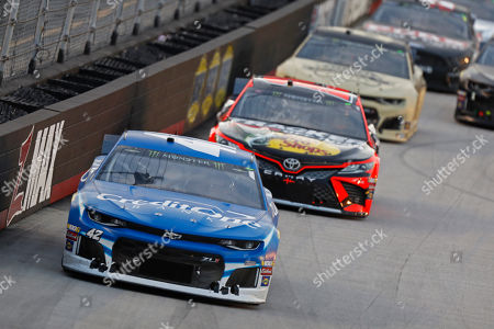 Driver Kyle Larson (42) leads others down the back straight during a NASCAR Cup Series auto race, in Bristol, Tenn