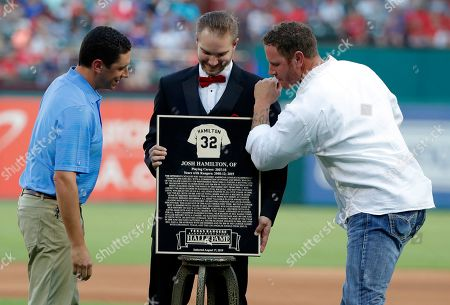 Josh Hamilton, Jon Daniels. Texas Rangers general manager Jon Daniels smiles as former player Josh Hamilton, right, pretends to put a shine on a plaque presented to him during a club Hall of Fame ceremony before the team's baseball game against the Minnesota Twins in Arlington, Texas