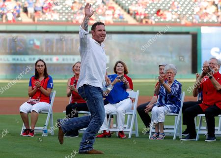 Former Texas Rangers player Josh Hamilton jogs onto the field for club Hall of Game ceremony where Hamilton and former Arlington Mayor Richard Greene were honored, before the team's baseball game against the Minnesota Twins in Arlington, Texas