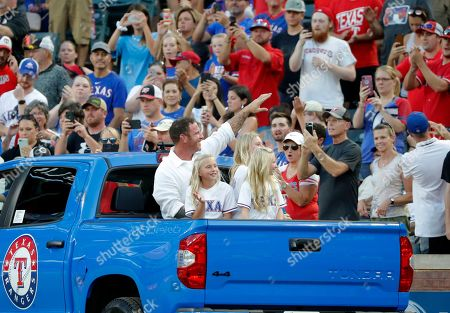 Former Texas Rangers player Josh Hamilton sits in the back of a truck with his daughters as he waves at fans after a club Hall of Fame ceremony before the team's baseball game against the Minnesota Twins in Arlington, Texas, . Hamilton and former Arlington Mayor Richard Greene were inducted in the ceremony