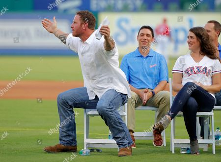 Jon Daniles, Josh Hamilton. Former player Josh Hamilton, center, gestures as his former teammate Michael Young makes comments during a club hall of fame induction ceremony where Hamilton was honored before a baseball game against the Minnesota Twins in Arlington, Texas,. Team president and general manager Jon Daniels, rear, look on during the ceremony