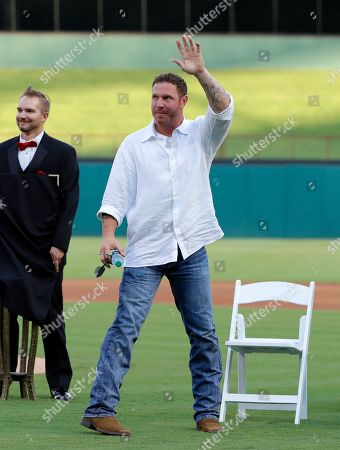 Former Texas Rangers player Josh Hamilton acknowledges cheers from fans during a club hall of fame induction ceremony where Hamilton was honored before a baseball game against the Minnesota Twins in Arlington, Texas
