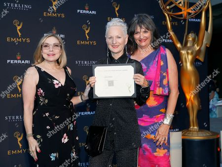 "Television Academy Costume Design Governors Laura Guzik, left, and Terry Ann Gordon, right, present costume designer Lou Eyrich with an Emmy nominee certificate for ""Pose"" at the 13th Annual Art of Television Costume Design at FIDM Museum & Galleries on in Los Angeles"