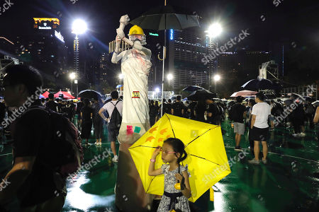 A girl carrying an umbrella walks past a replica of the Goddess of Democracy at Victoria Park in Hong Kong, . Protesters turned Hong Kong streets into rivers of umbrellas Sunday as they marched from a packed park and filled a major road in Hong Kong, where mass pro-democracy demonstrations have become a regular weekend activity over the summer